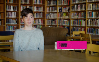 Boy named Tommy in school library speaking into a camera for an interview.