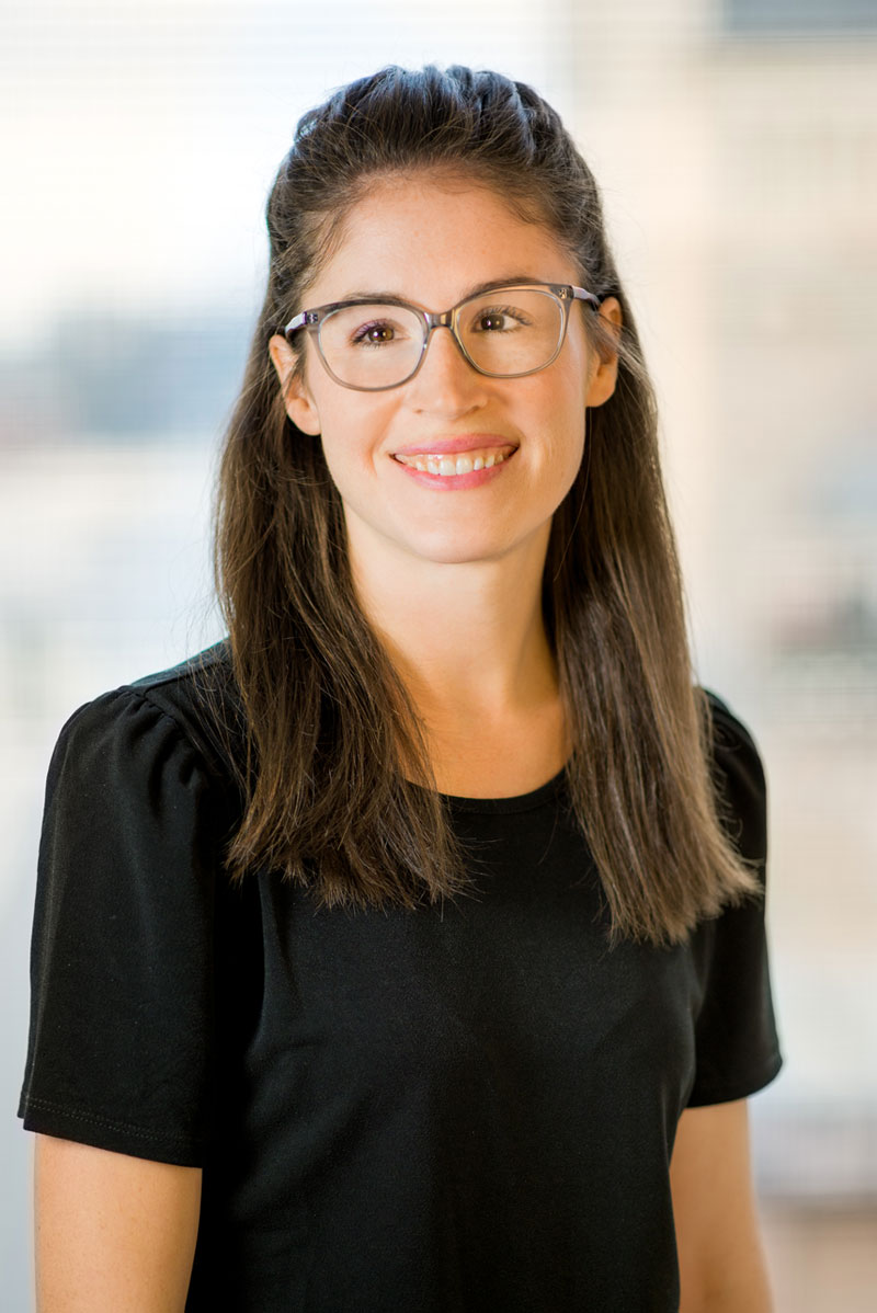 Headshot of Kelli Schlegelmilch, a woman with long, straight brunette hair and grey glasses, wearing a black tshirt