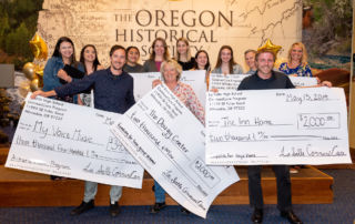 A group of students and nonprofit grant recipients holding large checks on stage at the CommuniCare Grant Awards Ceremony.