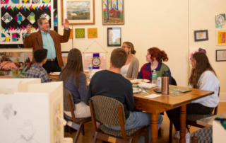 Jordan D. Schnitzer speaking in front of a group of six young students sitting at a wooden table in Pendleton, Oregon