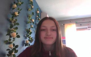 girl in her bedroom looking into a computer web cam